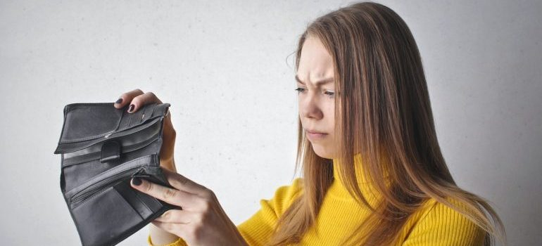 A woman looking into her wallet and frowning.