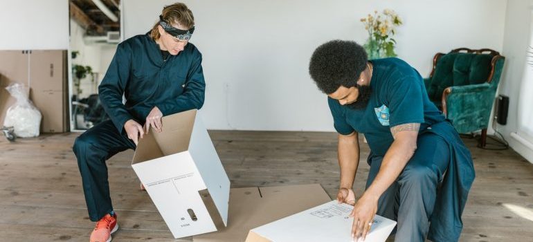 Two movers assembling boxes and helping in moving your office efficiently